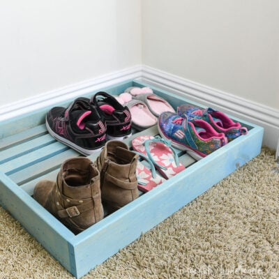 Turquoise stained shoe storage tray in the bottom of a kids closet.
