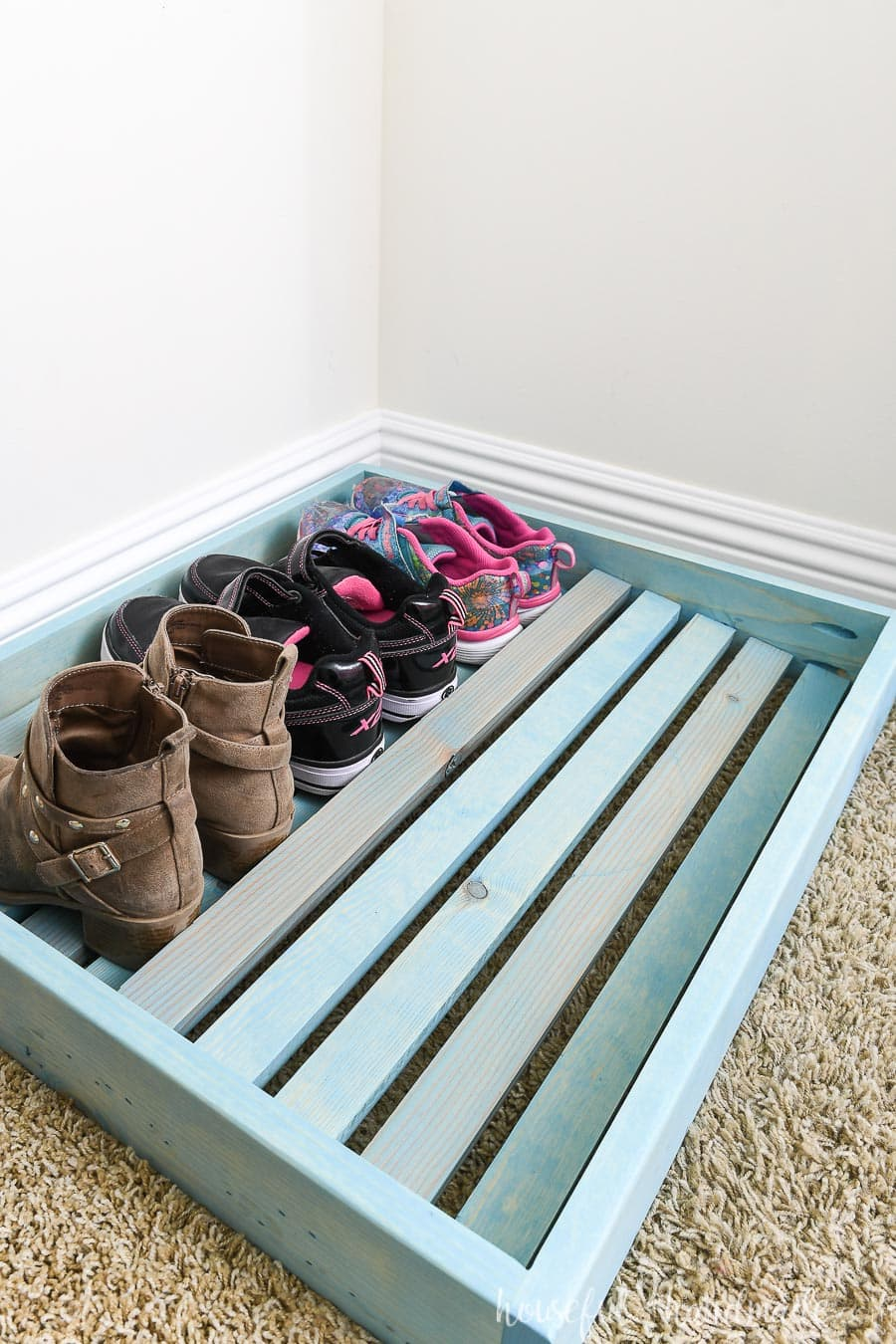 Shoe organizer tray with shoes on the back row showing the way the shoes sit in the organizer.