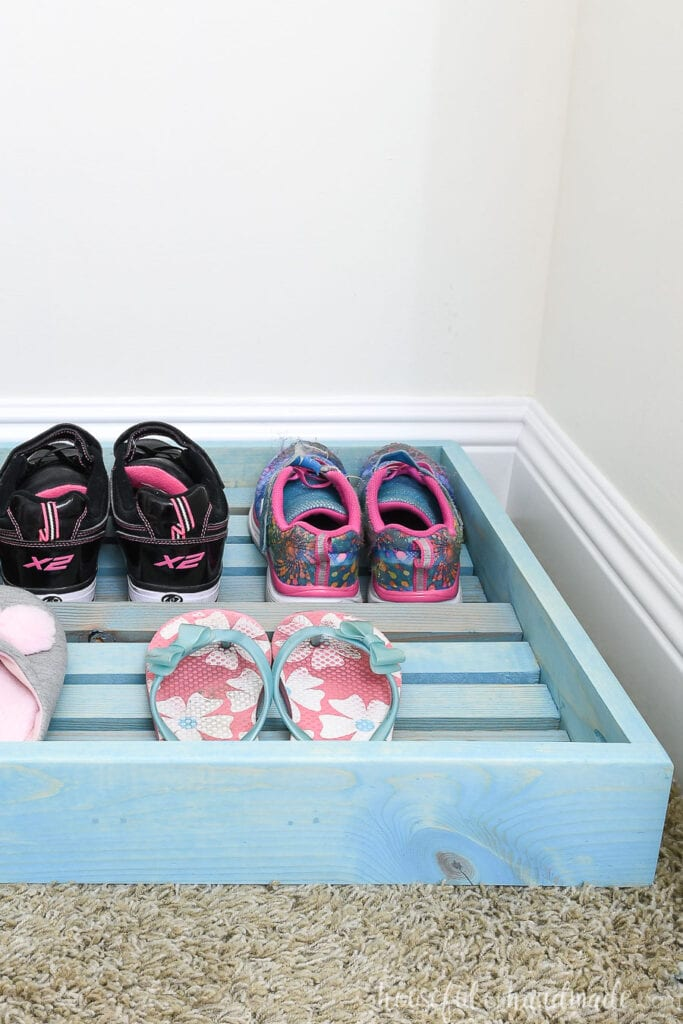 Side of the closet shoe organizer with shoes on the rows.