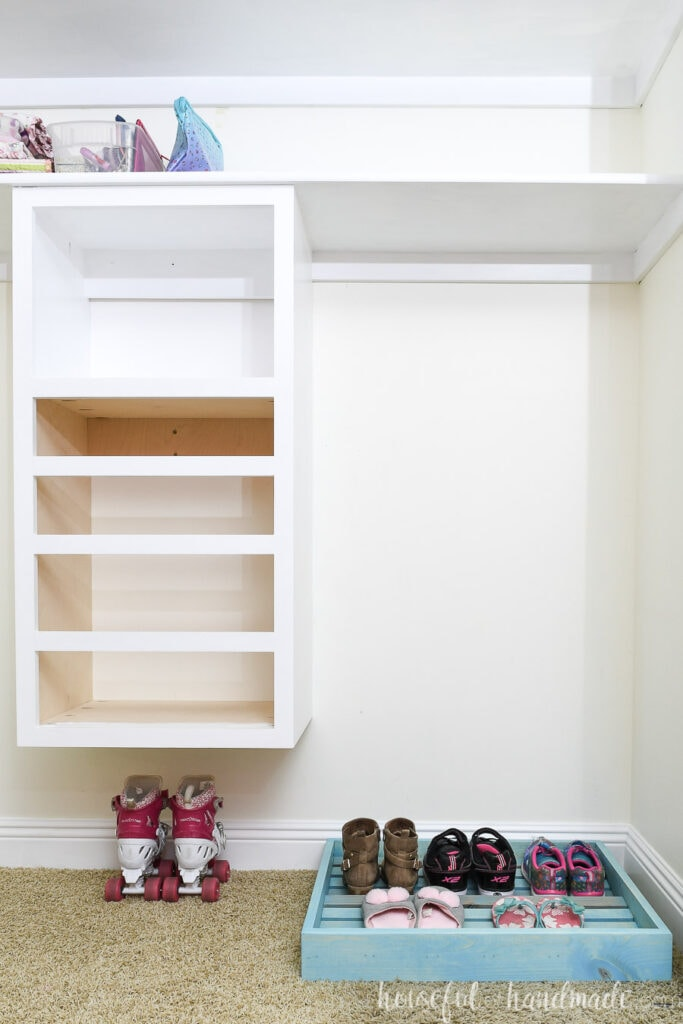Closet makeover on week 3 with closet organizer installed and painted and shoe organizer tray on the floor.