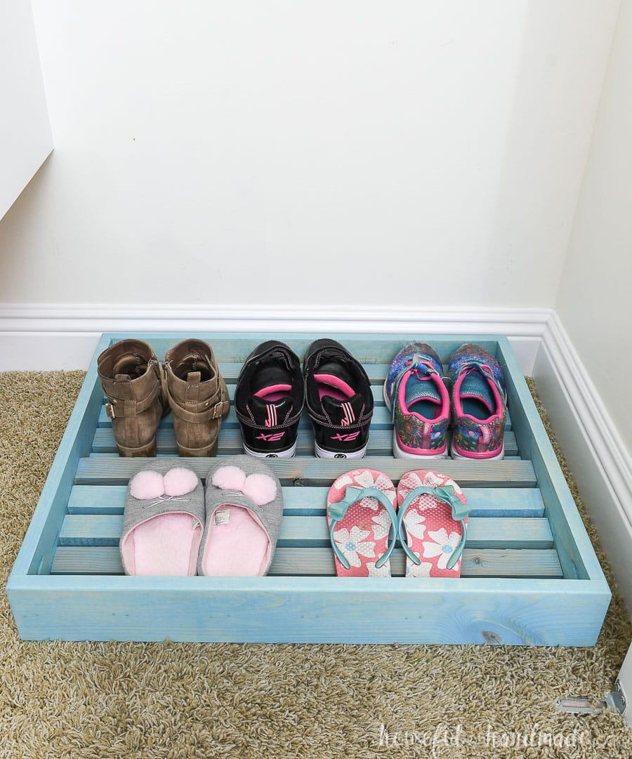Turquoise stained wood shoe rack in the closet.