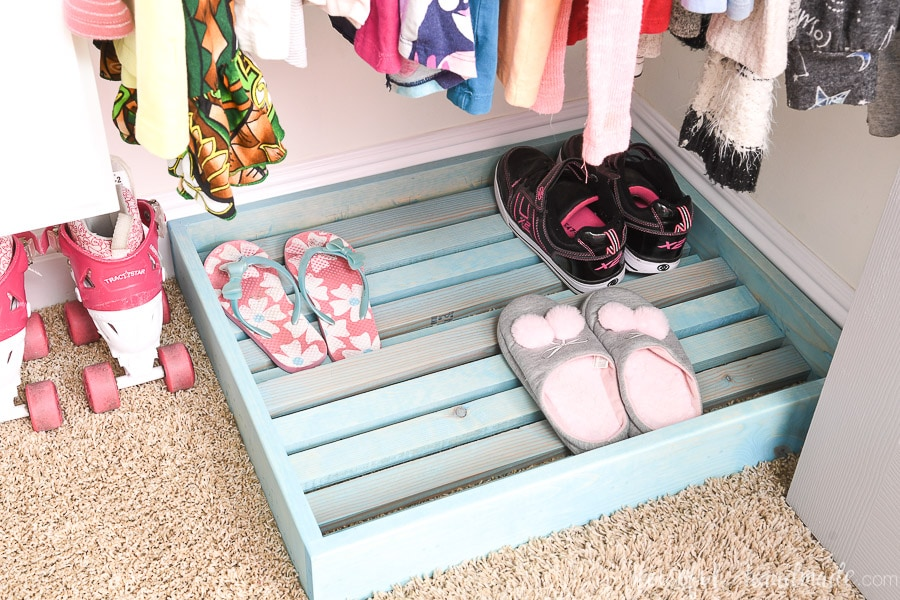 Shoe rack in the bottom of the closet with shoes and slippers on it.