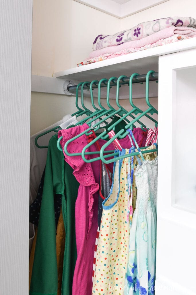 Closet rod with dresses hanging on teal hangers.