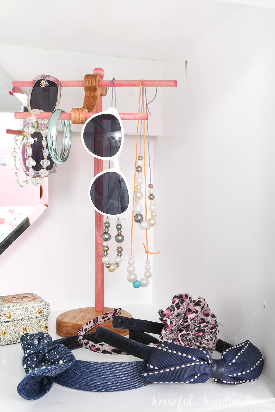 Wooden jewelry stand with kids bracelets, necklaces and sunglasses hanging on it.