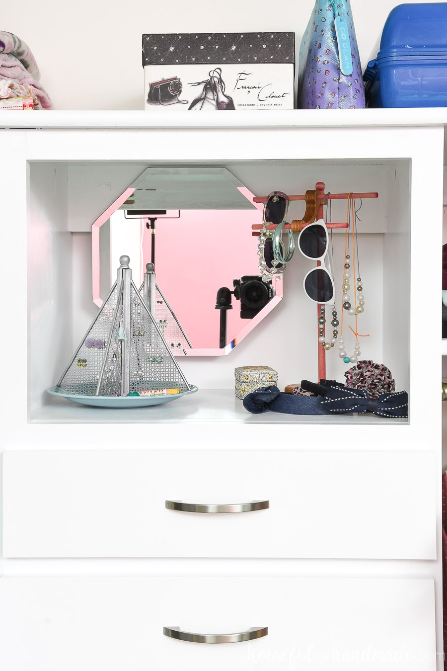 The top shelf of the closet organizer with jewelry organization for a girl.