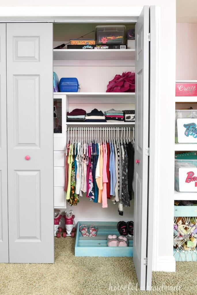 Girls organized closet with gray closet doors, one which is open showing the clothes hanging inside.