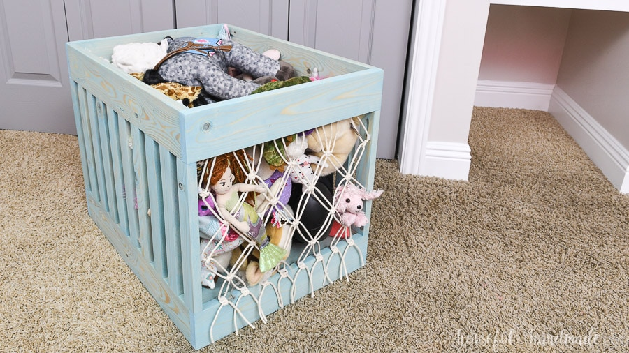 Macrame toy bin full of stuffed animals pulled out of the shelf nook.