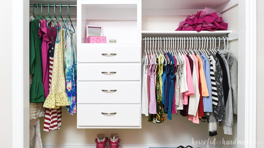 Kids closet organized with double hang bars and a DIY closet organizer in the center.