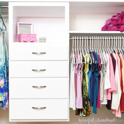 White DIY closet organizer with drawers inside a children's closet with clothes handing around it.