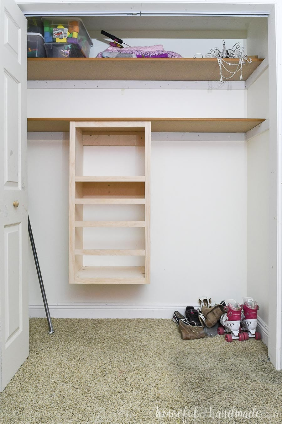 Kids closet cleared out of clothes with a DIY closet organizer added below the shelf.