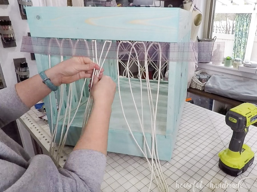 Starting the macrame net on the storage bin with the 4 center cords.