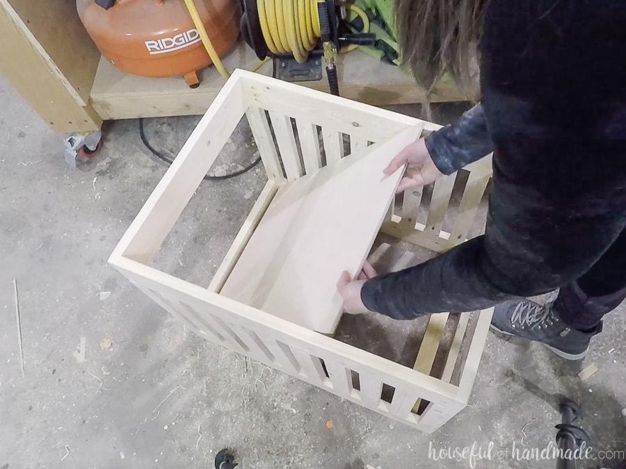 Adding the plywood bottom to the stuffed animal storage bin.