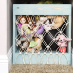Macrame net on the front of a wooden crate to hold stuffed animals.