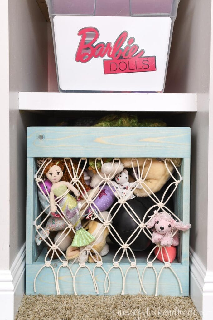Shelving nook next to closet with Barbie bin and DIY stuffed animal storage with macrame front in it.