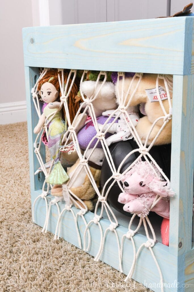 Close up view of the macrame net holding stuffed animals in the storage bin.