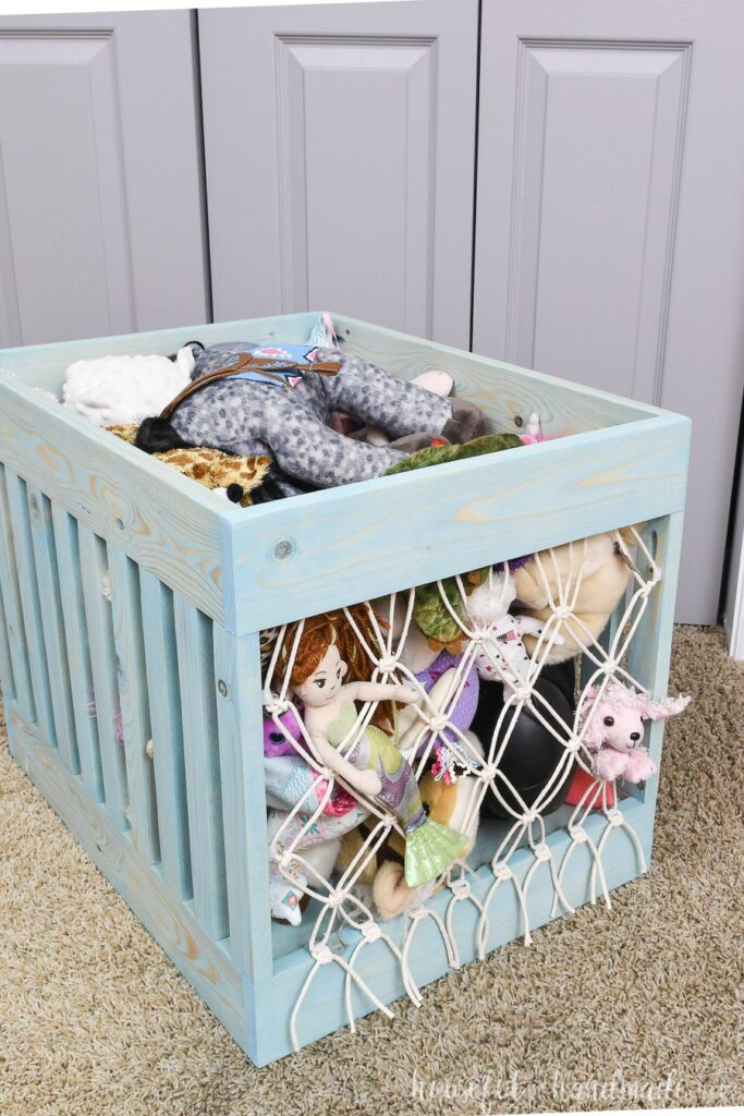 Turquoise stained wood bin turned into stuffed animal storage with a simple macrame net on the front & back.