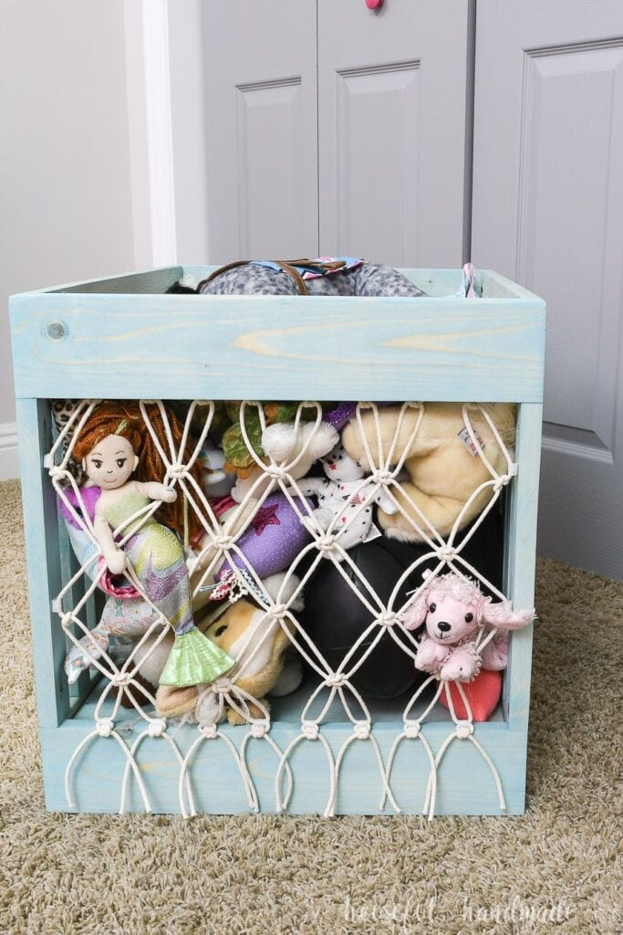DIY stuffed animal storage made from turquoise stained wood with a macrame tied net on the front and back.