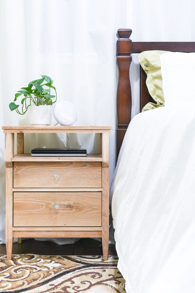 Gorgeous DIY solid wood nightstand next to bed with white duvet.