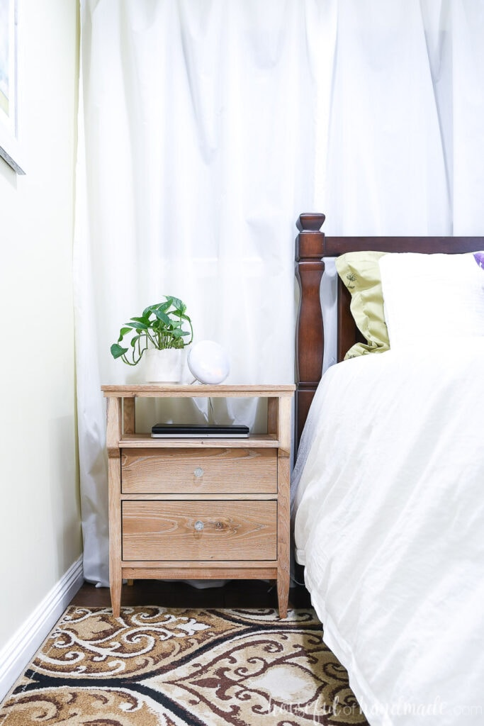 DIY tall nightstand with a plant on top next to the bed.