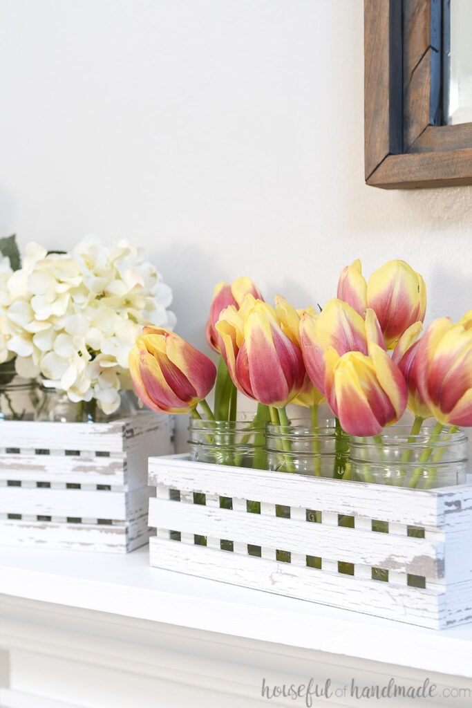 Two white chippy paint trough boxes on the mantel with mason jars filled with flowers inside.