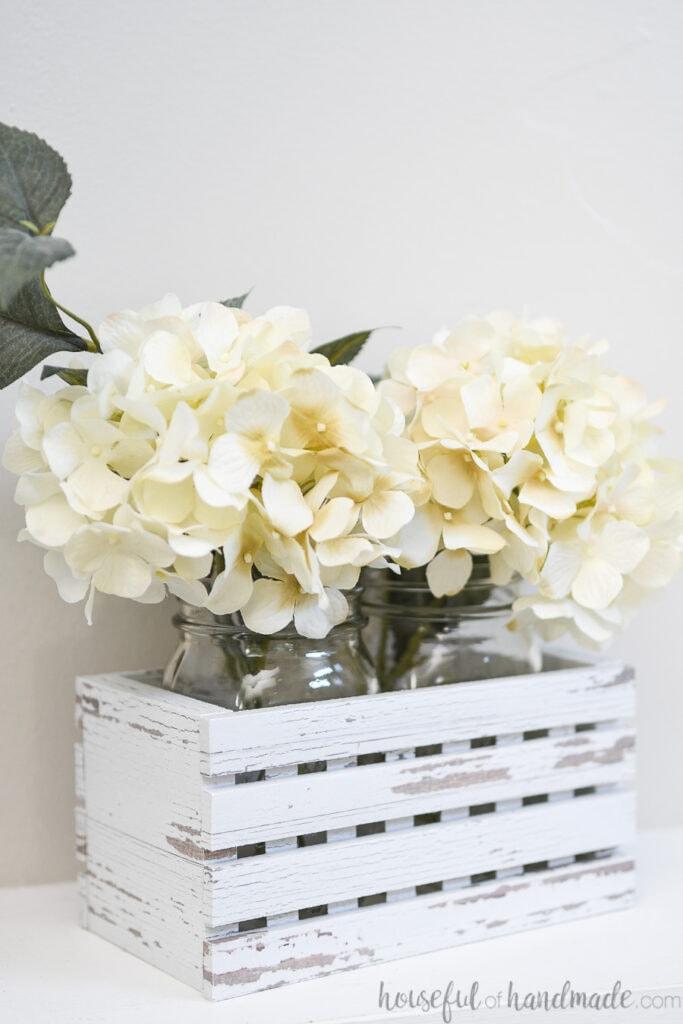 White hydrangea inside quart mason jars in a decorative farmhouse trough.