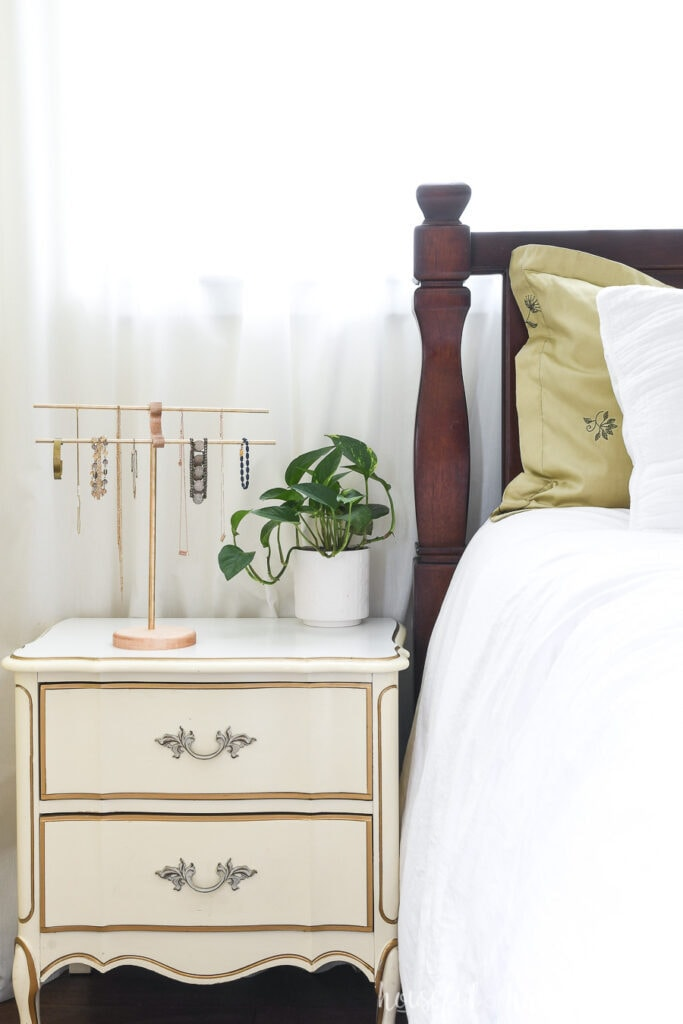 Bedroom nightstand with brass and wood necklace holder and potted plant on it.