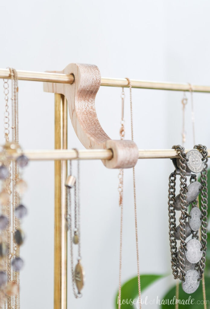Close up view of the center piece of the DIY necklace holder with brass rods.
