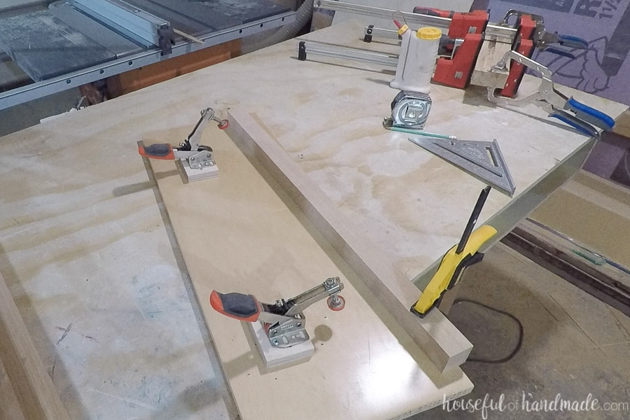2x2 leg piece clamped to plywood to make a tapered leg jig.