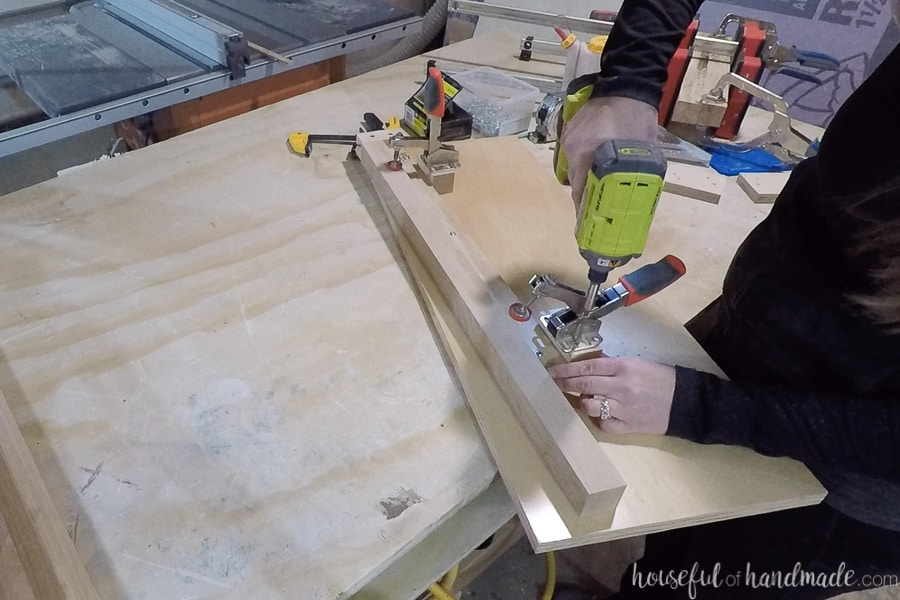 Screwing down self-adjusting clamps on the jig to clamp down the 2x2 legs.
