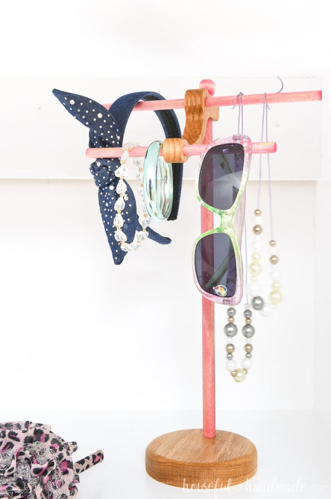 Pink and wood stained necklace holder with kids necklaces, sunglasses, and headbands on it.