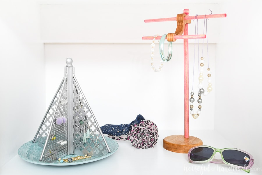 Two DIY jewelry holders in a closet displaying kids jewelry.