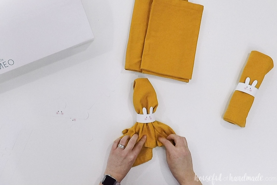 Straightening the yellow cloth napkin in the napkin ring.