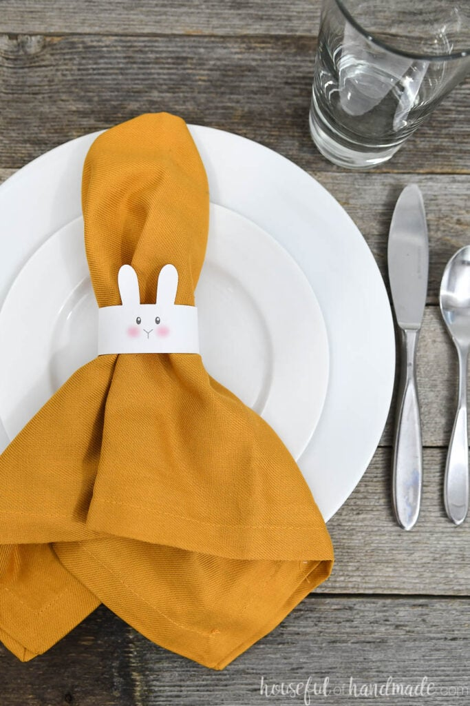 Table set with white plates and a paper bunny napkin ring on a napkin laying on top.