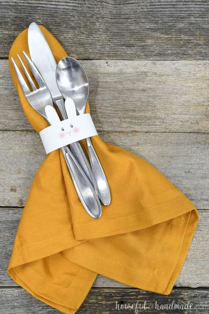 Yellow cloth napkin with bunny napkin ring around it and utensils tucked under the napkin ring.