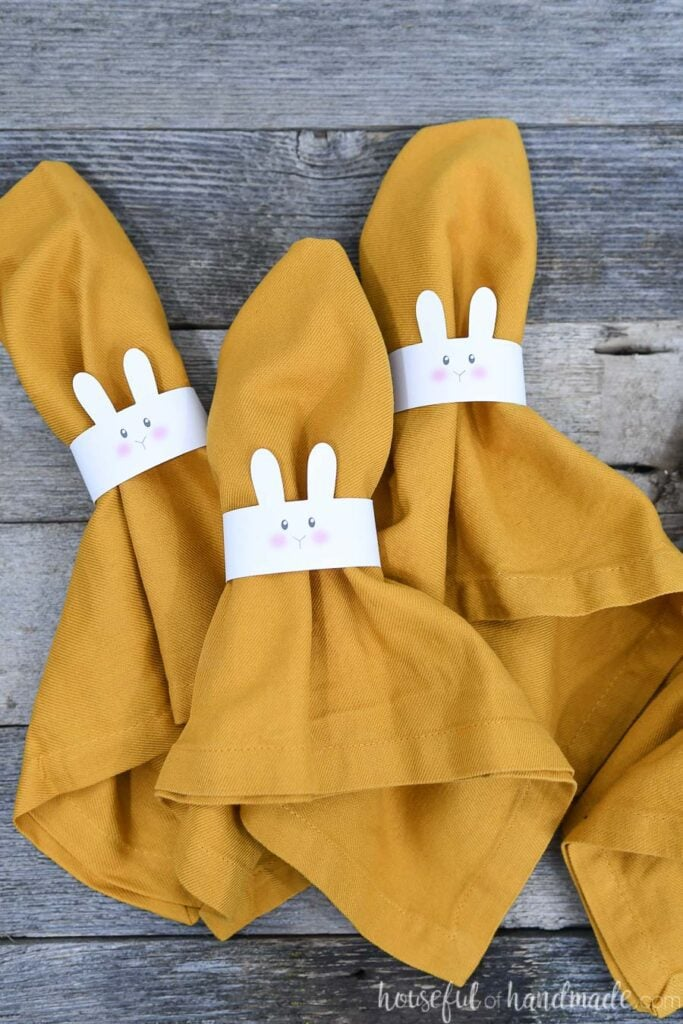 Four cloth napkins with bunny napkin rings around them.