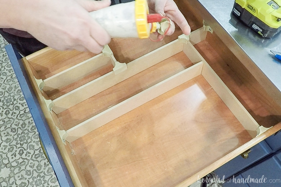 Adding glue to the inside of the wood clip to make them permanently attached to the drawer dividers.