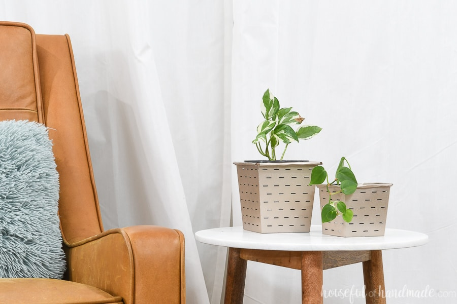 Leather chair next to table with paper flower pots covering budget potting containers.