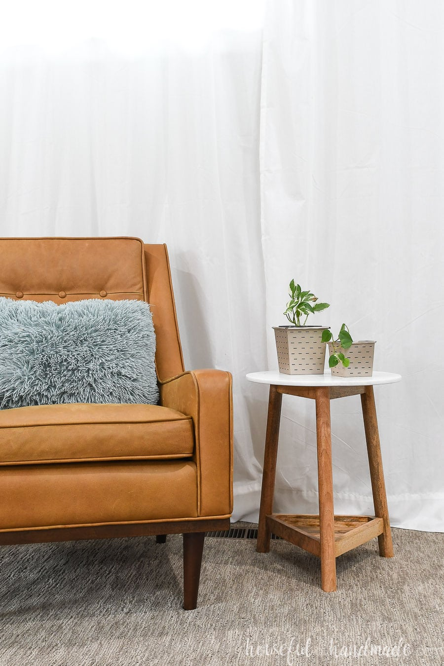 Living room with chair and end table holding houseplants in paper flower pots.