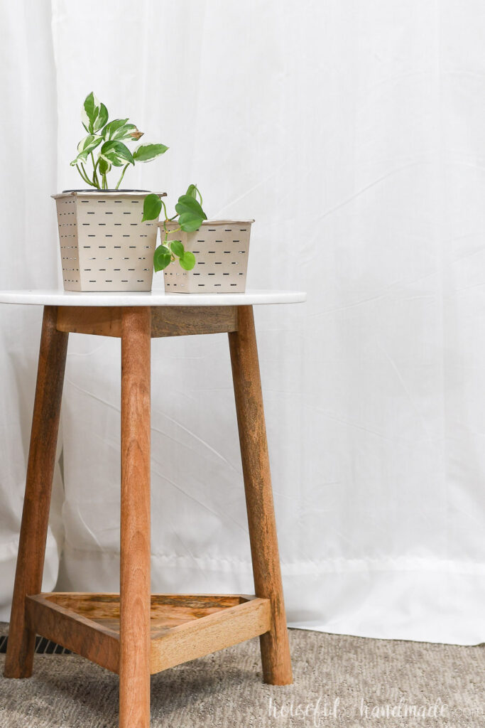 Two rose gold painted flower pots holding house plants on top of an end table.