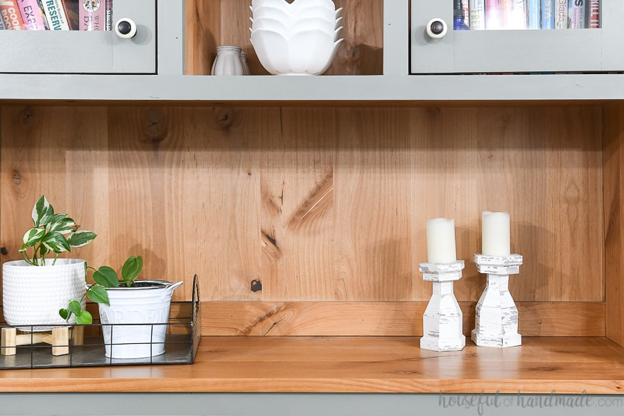 Two white chippy paint candlesticks in a hutch next to plants.