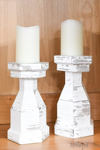 Two fab wood candlesticks with white candles on them.