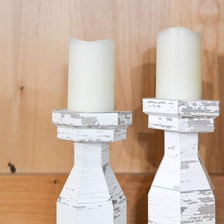 Two chunky candlesticks with chippy white paint texture in a bookcase.