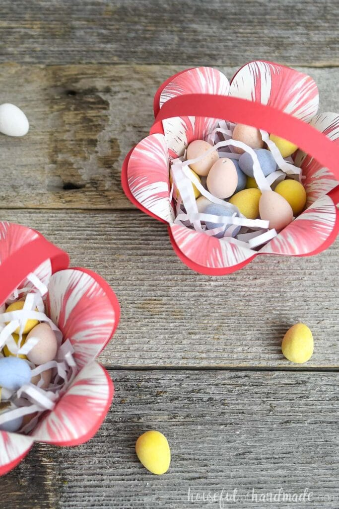 Two paper easter baskets that look like flowers filled with shredded paper and egg candies.