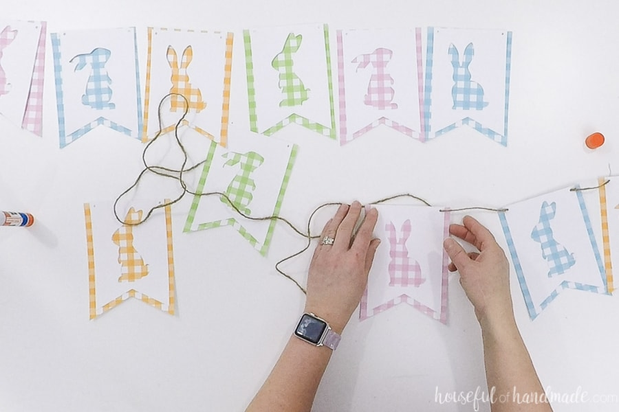 Threading the pieces of the gingham bunny banner onto twine.