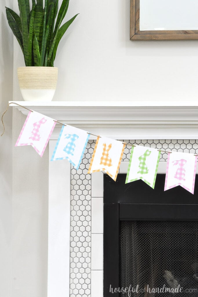 White tiled fireplace with gingham bunny banner hanging on the mantel.