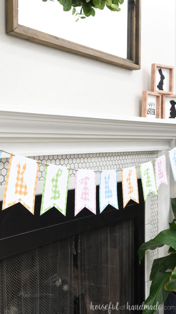 Angled view of the Easter banner with bunny silhouettes hanging on a mantel.