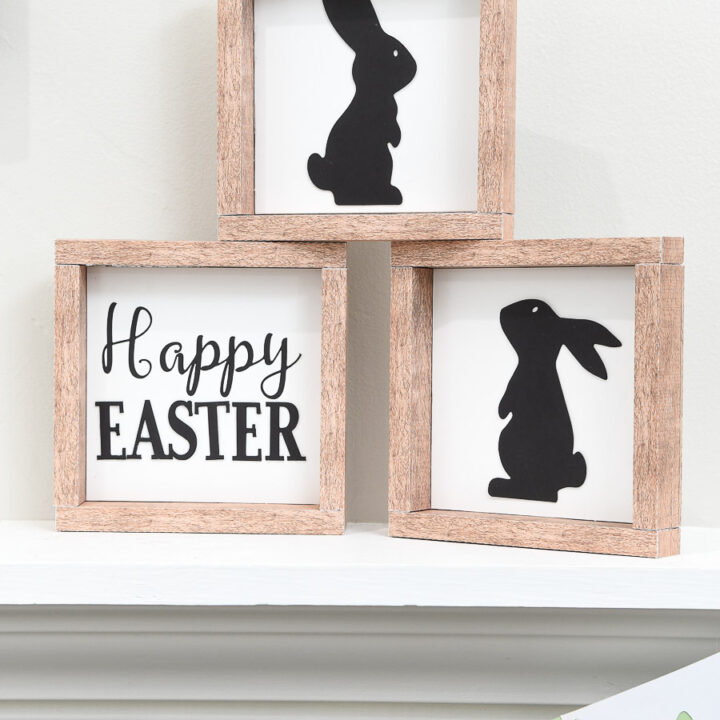 Three farmhouse Easter signs stacked in a pyramid on a shelf.