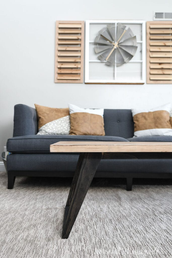 Coffee table with black legs and natural wood top in front of a sofa with pillows.