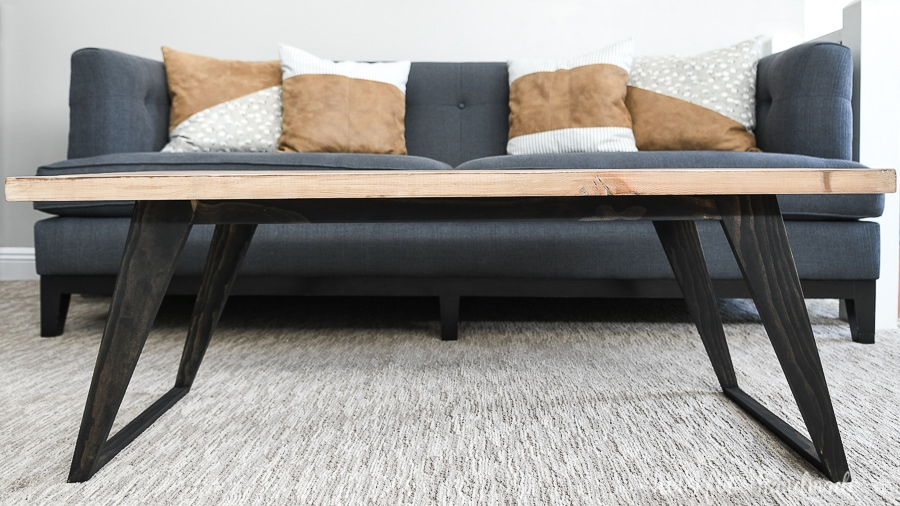 Straight on view of the modern coffee table with angled legs stained black and warm wood top.