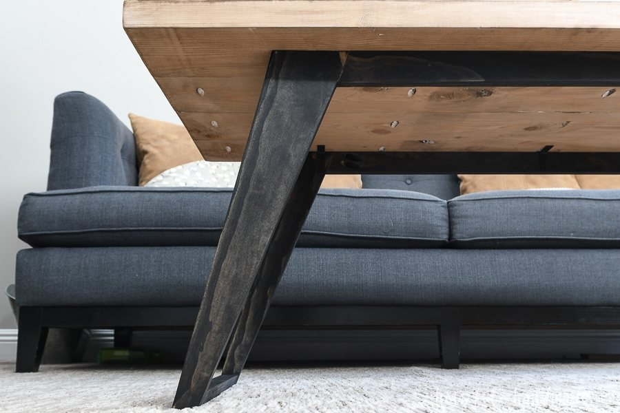 Close-up view of the angled and tapered legs attached to the underside of the coffee table top.